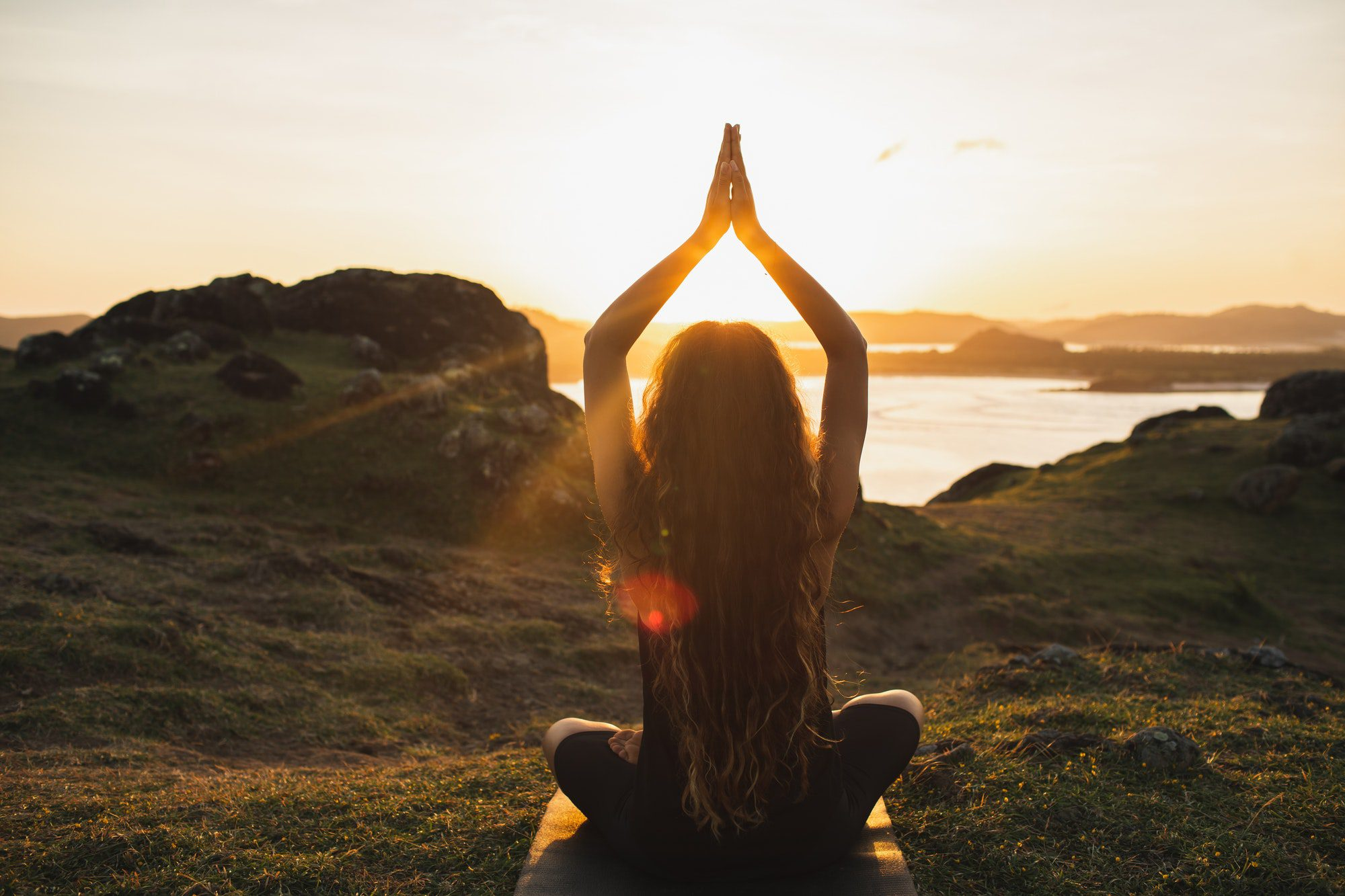 Young woman practicing yoga outdoors. Spiritual harmony, introspection and wellbeing concept